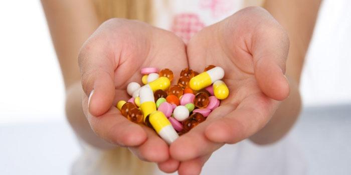 Таблетки и капсулы в руках  у девушки