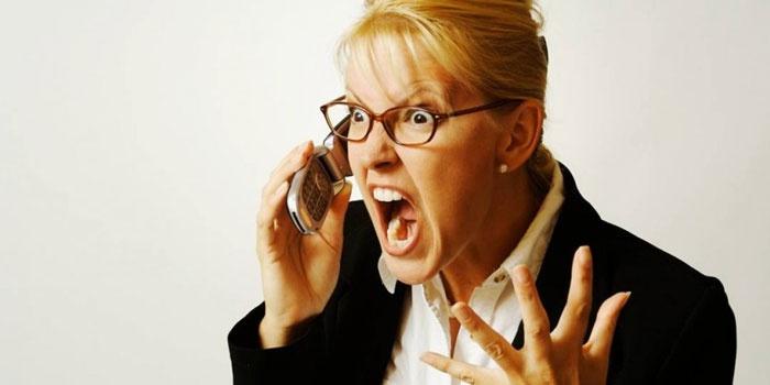 Женщина кричит вовремя разговора по телефону