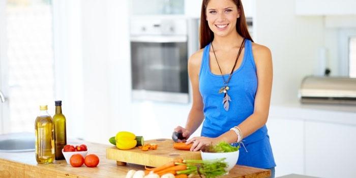 Девушка на кухне нарезает морковь