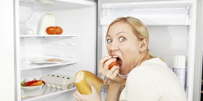 Девушка ест у холодильника