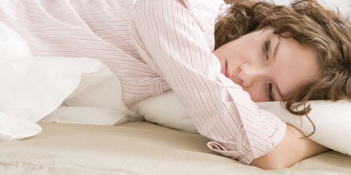 Молодая женщина лежит в постели