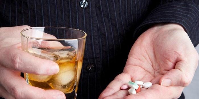 Таблетки в руке и стакан алкоголя