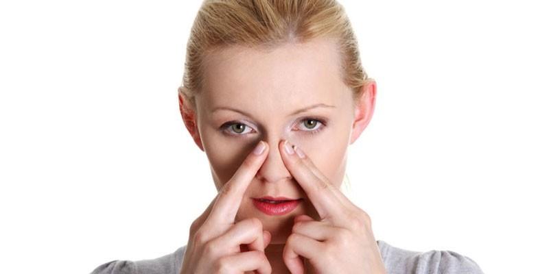 Женщина приложила пальцы к носу