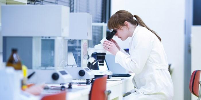 Лаборант проводит исследования под микроскопом