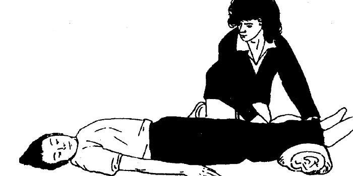Женщина подкладывает валик под ноги человека в обмороке