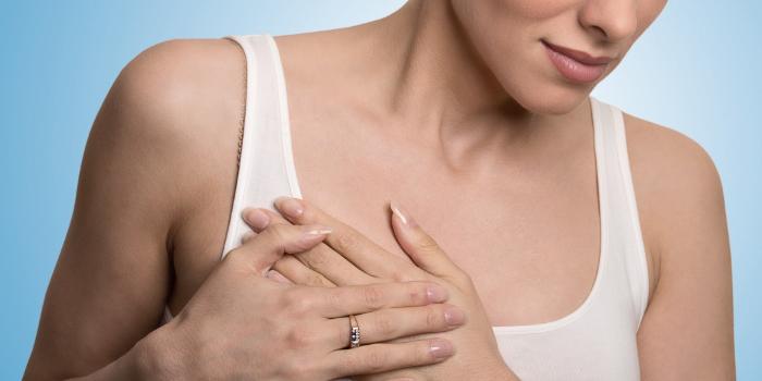 Девушка ощупывает грудь