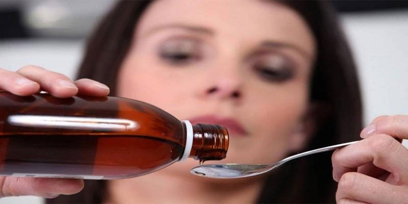 Женщина наливает сироп в ложку