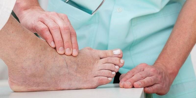 Медик осматривает ногу пациента