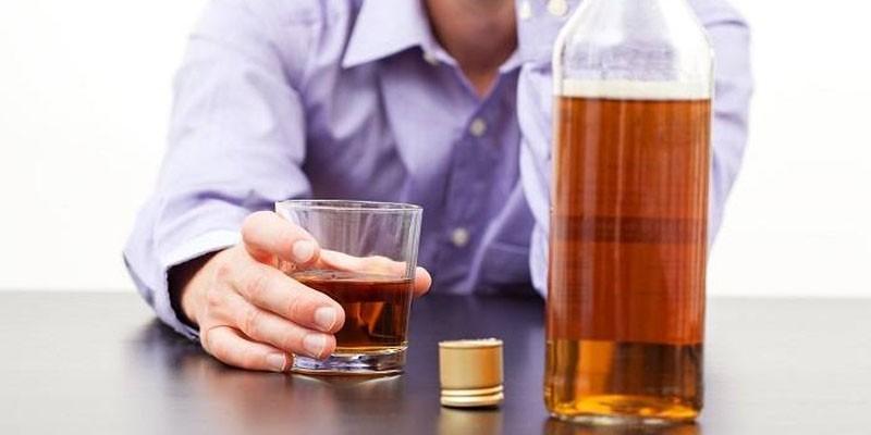 Мужчина со стаканом алкоголя в руке