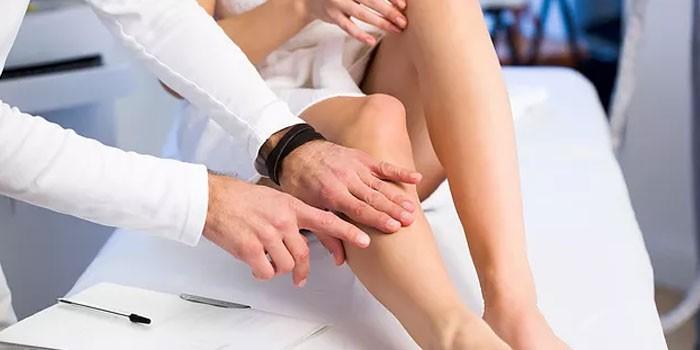 Ангиолог осматривает ноги пациентки