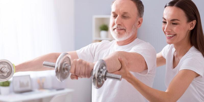 Человек занимается с тренером физическими упражнениями