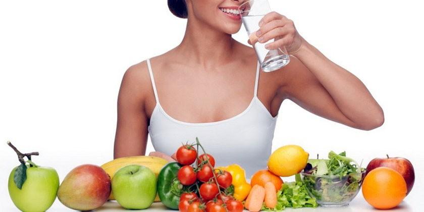 Фрукты и овощи на столе, девушка пьет воду