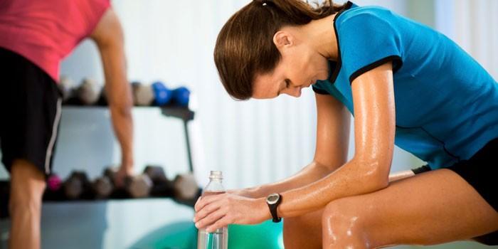 Девушка с бутылкой воды в спортзале