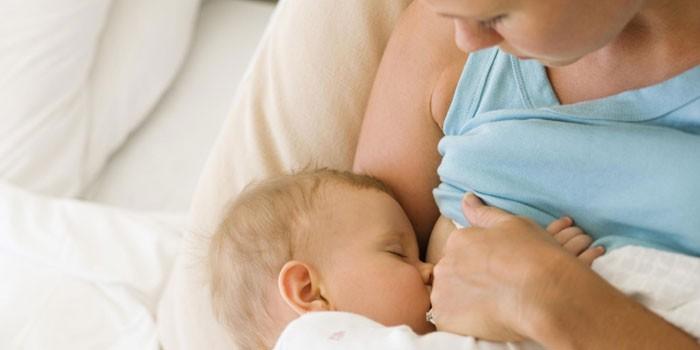 Женщина кормит грудью малыша