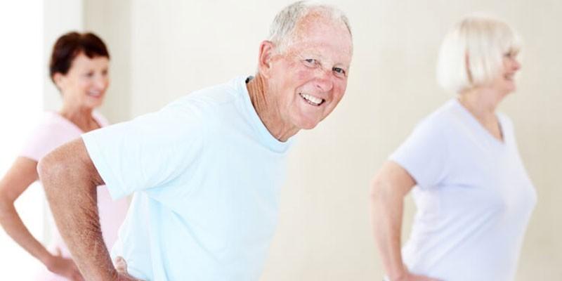 Пожилые люди выполняют упражнение