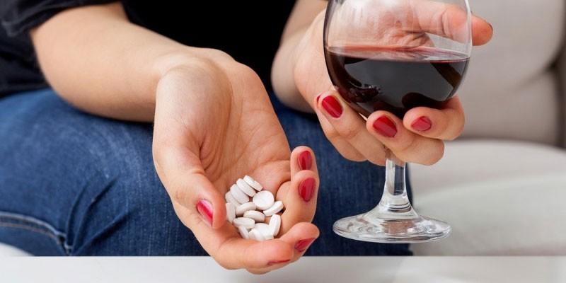 Медикаменты и бокал алкоголя в руках