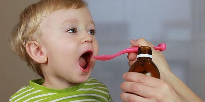 Ребенку дают микстуру от кашля