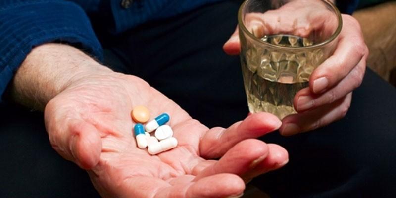 Лекарства и алкоголь в руках мужчины