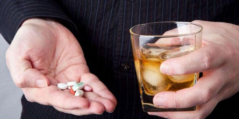 Таблетки и стакан виски в руках