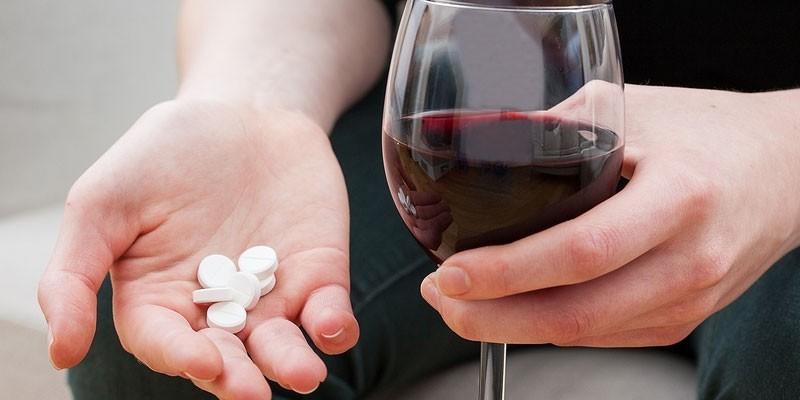 Таблетки и бокал вина в руках