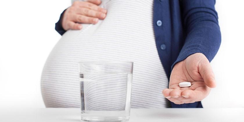 Беременная женщина с таблеткой на ладони и стакан воды