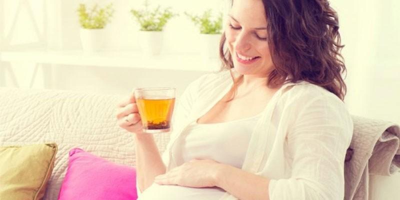 Беременная женщина с чашкой чая