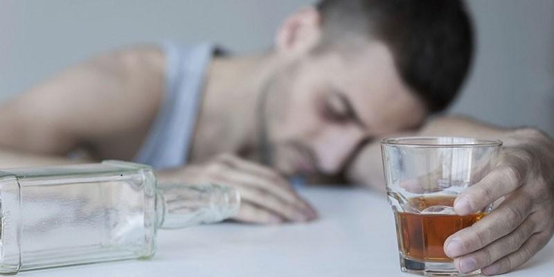 Парень спит на столе со стаканом алкоголя