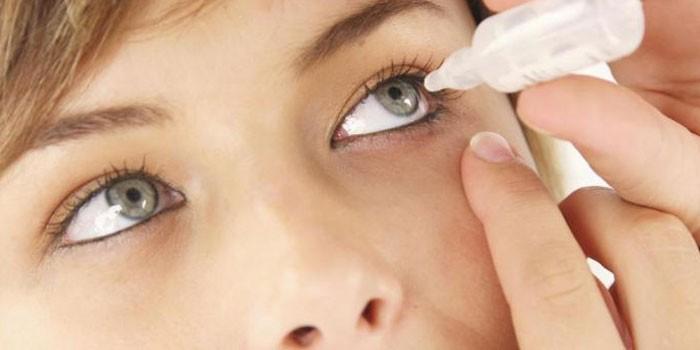Девушка закапывает капли глаз