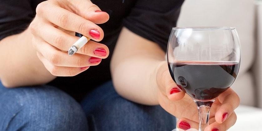 Женщина курит и пьет вино