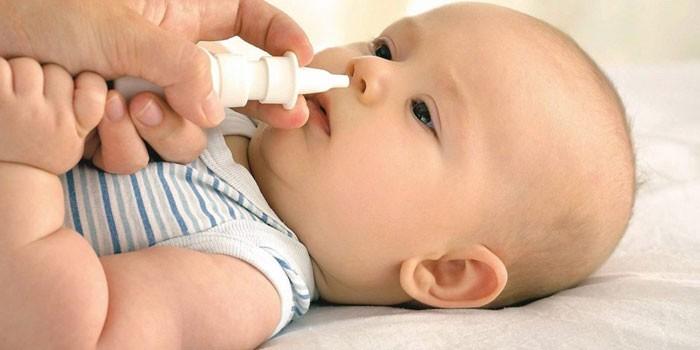 Малышу закапывают капли в нос