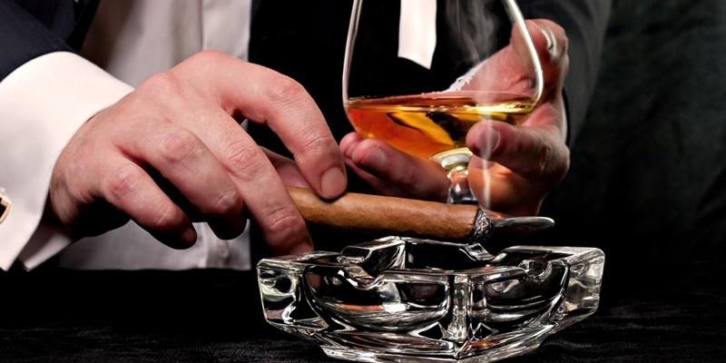 Мужчина курит и пьет коньяк