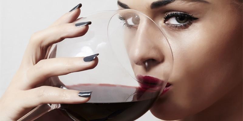 Женщина пьет вино из бокала