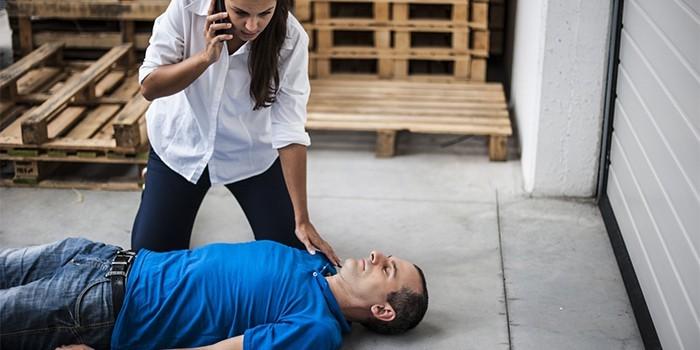 Мужчина без сознания и девушка с телефоном