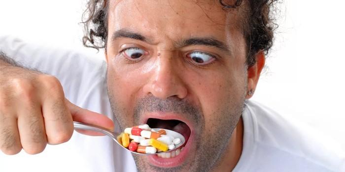 Мужчина ест таблетки ложкой