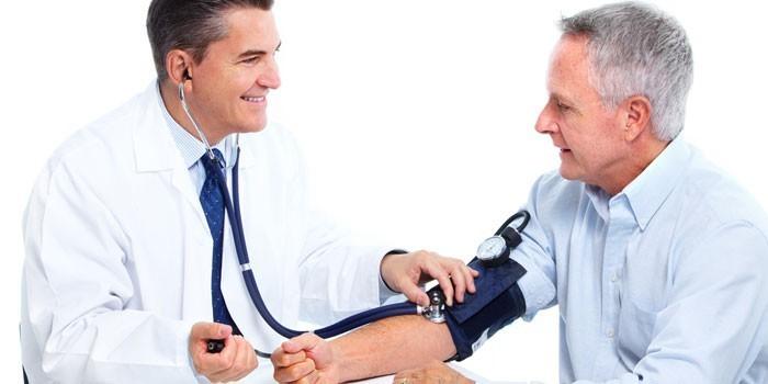 Медик измеряет давление пациенту