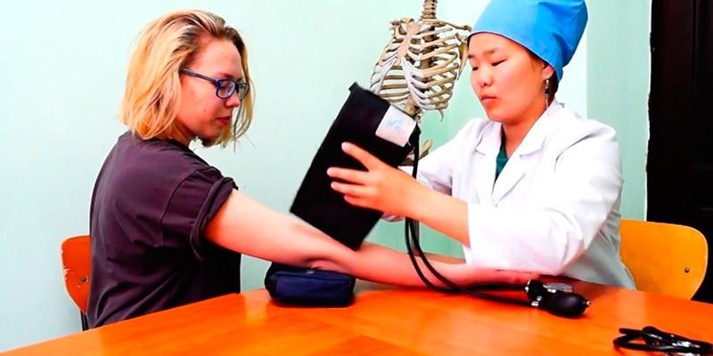 Медик надевает манжету тонометра на руку пациентки