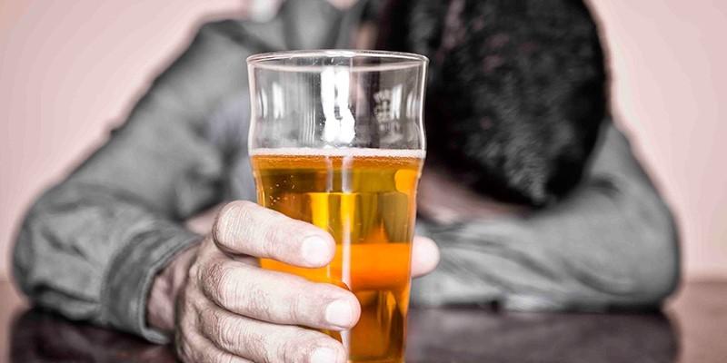 Человек со стаканом спиртного в руке