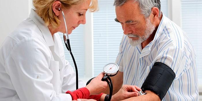 Медик измеряет пациенту давление