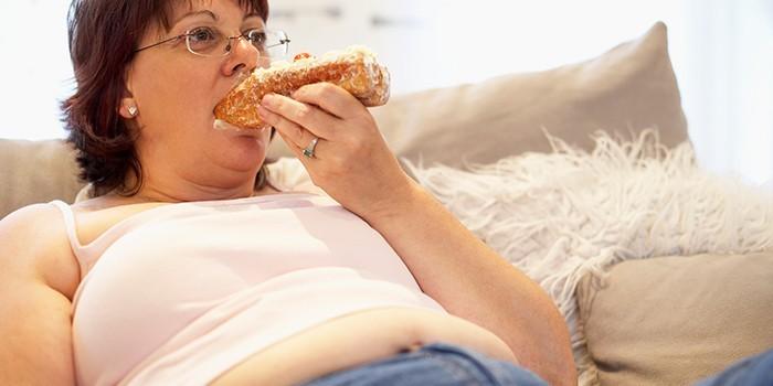 Женщина ест лежа на диване