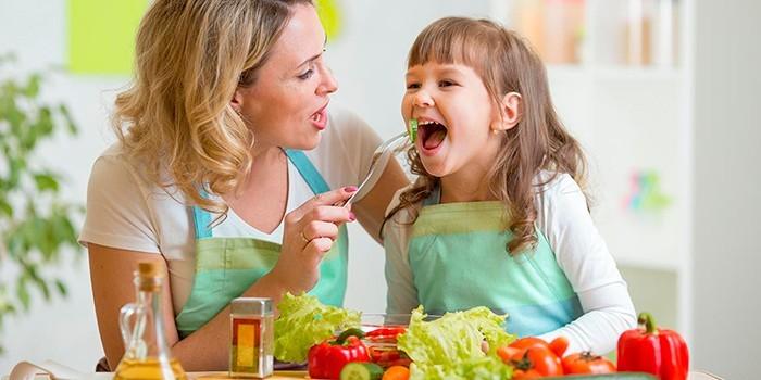 Женщина кормит ребенка овощами
