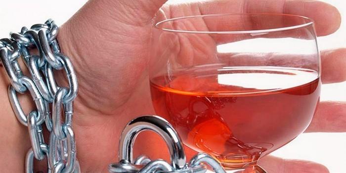 Рука прикованная к стакану с алкоголем