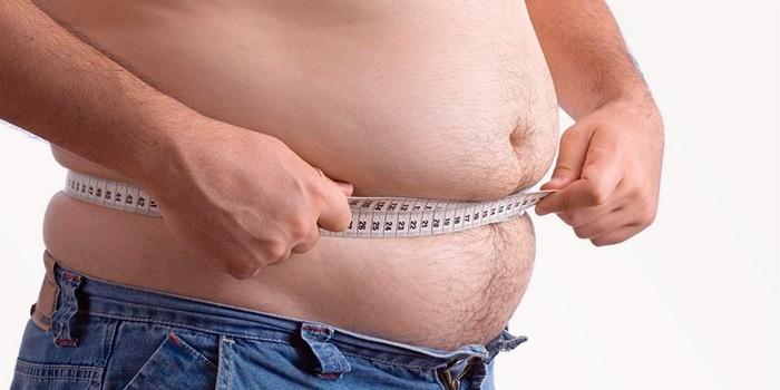 Мужчина измеряет талию