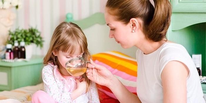 Мама дает девочке чай