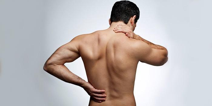 Мужчина приложил руки к спине