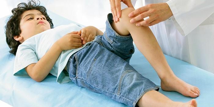 Врач осматривает ногу ребенка