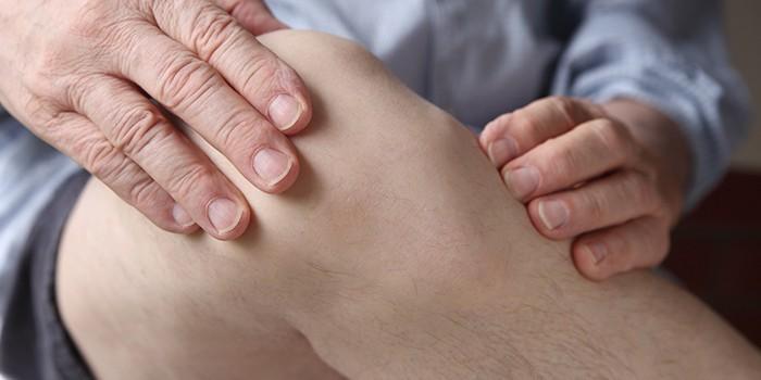 Человек ощупывает колено