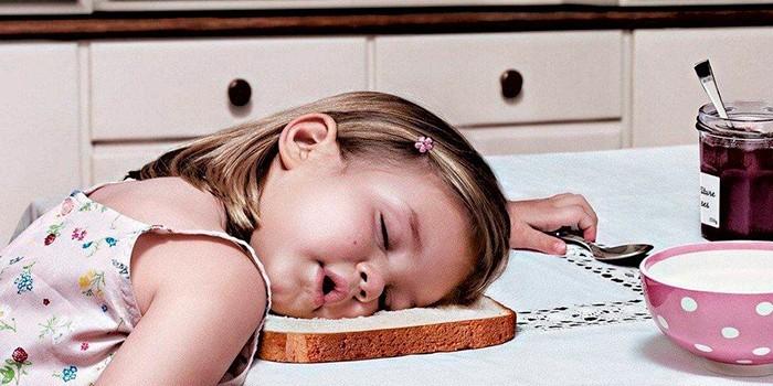 Девочка спит за столом