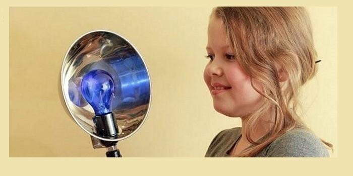 Девочка проходит прогревание синей лампой